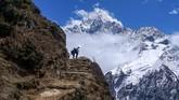 Dua orang pria berjalan di jalur pendakian yang sepi ditinggal pengunjung. (Photo by PRAKASH MATHEMA / AFP)