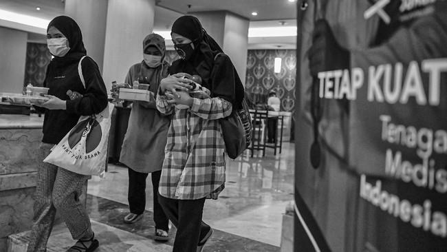 Petugas medis berjalan sambil membawa makanan di Hotel Grand Cempaka, Jakarta. (ANTARA FOTO/Nova Wahyudi)