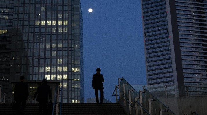 A man walks down the steps as the moon rises over buildings Monday, April 6, 2020, in Tokyo. Reports say Prime Minister Shinzo Abe plans to declare an emergency in Tokyo and other cities Tuesday. (AP Photo/Jae C. Hong)