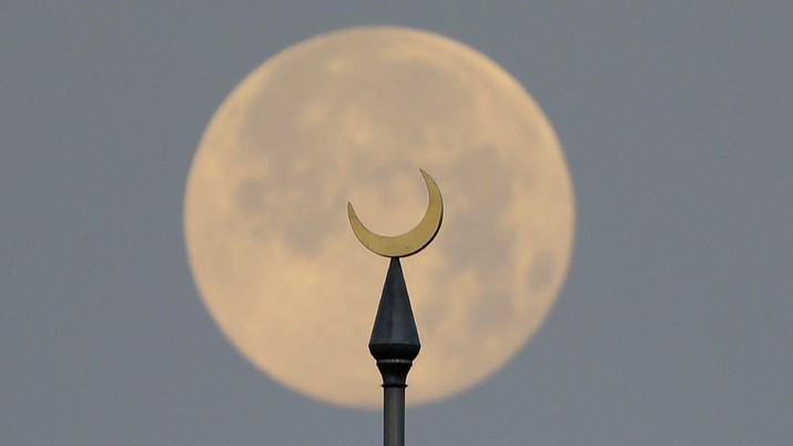 The full pink supermoon sets behind the minarets on the University of Tampa campus Wednesday, April 8, 2020, in Tampa, Fla. (AP Photo/Chris O'Meara)
