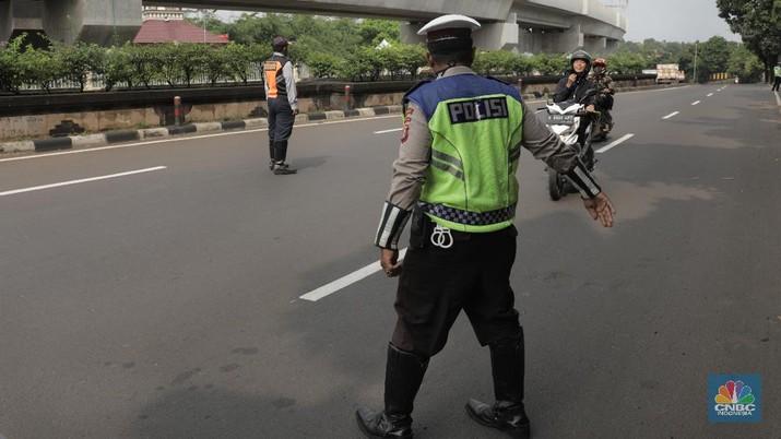 Polisi lalu lintas dan Dishub melaksanakan pengawasan dalam penerapan pembatasan sosial berskala besar (PSBB) di Jalan Lebak Bulus, Jakarta Selatan (10/4/2020). Polantas dan Dishub menyetop bagi pengendara motor atau mobil yang tidak menggunakan masker dan mengingatkan kewajiban warga untuk memakai masker dan aturan penumpang dalam satu kendaraan. (CNBC Indonesia/Muhammad Sabki)