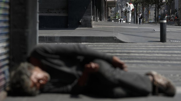 A city worker sprays disinfectant as a man sleeps on the street, in central Mexico City, Monday, April 6, 2020. Mexican President Andres Manuel Lopez Obrador said Sunday there will be no huge economic stimulus program as the country faces the threat of coronavirus-induced crisis almost certainly unlike any it has seen in the past century. (AP Photo/Rebecca Blackwell)