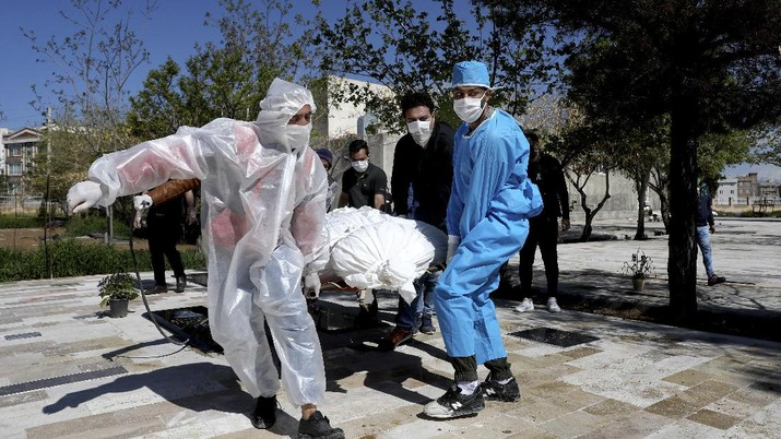 People wearing protective clothing carry the body of a victim who died after being infected with the new coronavirus at a cemetery just outside Tehran, Iran, Monday, March 30, 2020. The new coronavirus causes mild or moderate symptoms for most people, but for some, especially older adults and people with existing health problems, it can cause more severe illness or death. (AP Photo/Ebrahim Noroozi)
