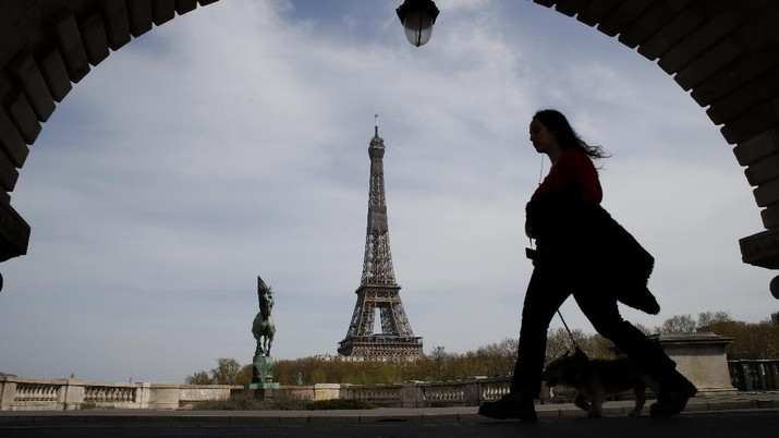 A woman walks her dog on a Paris bridge, with the Eiffel tower seen in background, during a nationwide confinement to counter the COVID-19, Tuesday, April 7, 2020. The new coronavirus causes mild or moderate symptoms for most people, but for some, especially older adults and people with existing health problems, it can cause more severe illness or death. (AP Photo/Christophe Ena)