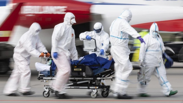 A patient from France who is seriously ill with the coronavirus is transported from an ambulance plane after landing at Dresden International Airport in Dresden, Germany, Saturday, April 4, 2020. For most people, the new coronavirus causes only mild or moderate symptoms, such as fever and cough. For some, especially older adults and people with existing health problems, it can cause more severe illness, including pneumonia.(Robert Michael/dpa via AP)