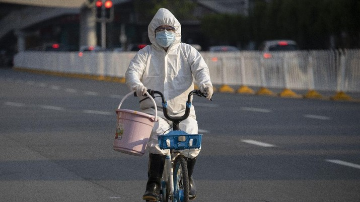 A resident wearing mask and suit against the coronavirus cycles in Wuhan in central China's Hubei province on Sunday, April 12, 2020. For most people, the new coronavirus causes only mild or moderate symptoms. For some it can cause more severe illness. (AP Photo/Ng Han Guan)