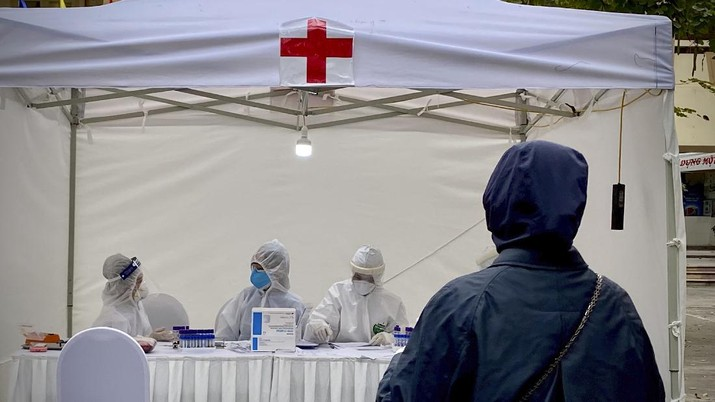 A woman provides test samples at a makeshift COVID-19 testing facility in Hanoi, Vietnam, on Tuesday, Mar. 31, 2020. Vietnam has set up its first makeshift facilities for fast coronavirus testing in residential areas in an effort to detect early infections. (AP Photo/Hau Dinh)