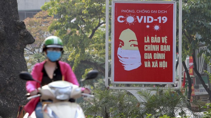 A motorcyclist drives past a poster calling people to take care of their health against the new coronavirus in Hanoi, Vietnam Tuesday, April 14, 2020. The new coronavirus causes mild or moderate symptoms for most people, but for some, especially older adults and people with existing health problems, it can cause more severe illness or death. (AP Photo/Hau Dinh)