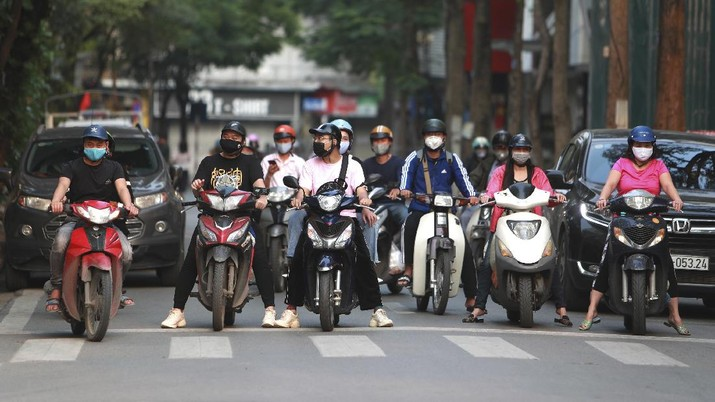 Motorcyclists wearing masks stop at for traffic lights in Hanoi, Vietnam Tuesday, April 14, 2020. The new coronavirus causes mild or moderate symptoms for most people, but for some, especially older adults and people with existing health problems, it can cause more severe illness or death. (AP Photo/Hau Dinh)