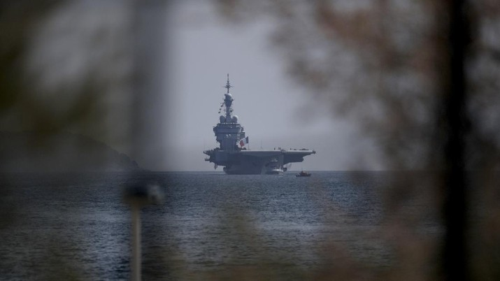 The French aircraft carrier Charles de Gaulle arrives in the bay of Toulon, southern France, Sunday April 12, 2020. The Defense Ministry said in a statement that around 40 sailors showed symptoms compatible with COVID-19, the disease the coronavirus causes. The new coronavirus causes mild or moderate symptoms for most people, but for some, especially older adults and people with existing health problems, it can cause more severe illness or death. (AP Photo/Daniel Cole)