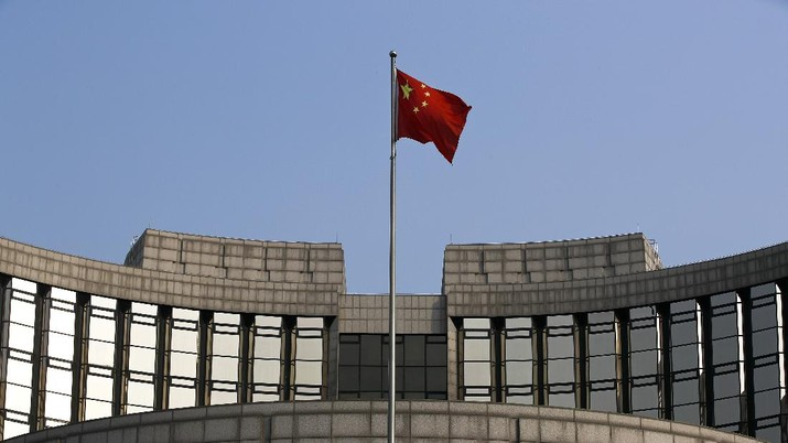 A man walks past China's central bank, or the People's Bank of China, in Beijing, Sunday, March 10, 2019. China's central bank governor Yi Gang says American and Chinese envoys discussed sticking to promises to avoid currency devaluations to boost exports during negotiations aimed at ending a tariff war. (AP Photo/Andy Wong)