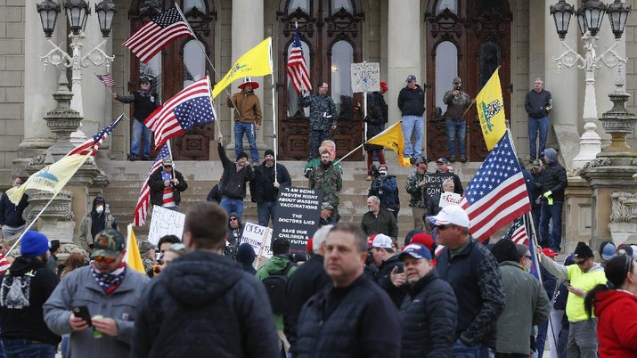A Trump Unity sign on a trailer is shown parked at a protest in front of the Michigan State Capitol in Lansing, Mich., Wednesday, April 15, 2020. Flag-waving, honking protesters drove past the Michigan Capitol on Wednesday to show their displeasure with Gov. Gretchen Whitmer's orders to keep people at home and businesses locked during the new coronavirus COVID-19 outbreak. (AP Photo/Paul Sancya)