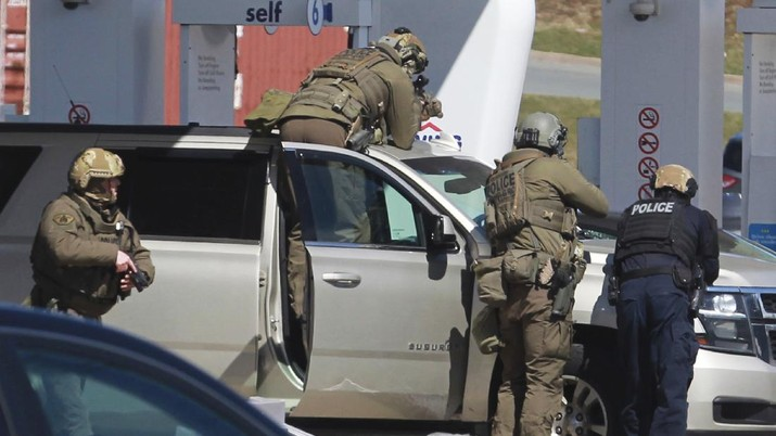 A worker with the medical examiner's office removes a body from a gas bar in Enfield, Nova Scotia, on Sunday, April 19, 2020. A suspect in an active shooter investigation was placed in custody Sunday at an Irving service station in Nova Scotia, after police said there were