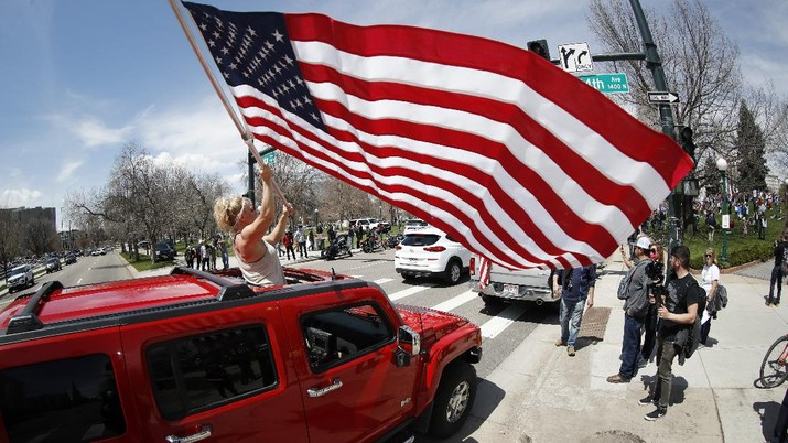 A protester stands out of the sunroof of a sports-utility vehicle to wave an American flag during a car protest against the stay-at-home order issued by Colorado Governor Jared Polis to stem the spread of the new coronavirus Sunday, April 19, 2020, in Denver. (AP Photo/David Zalubowski)