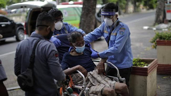 Deteksi kesehatan dini yang dilakukan petugas antara lain mengecek suhu badan, serta menanyakan kondisi yang tengah dirasakan tunawisma tersebut pada tubuhnya. (CNNIndonesia.com/Adhi Wicaksono)