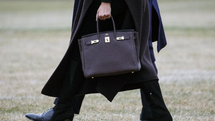 President Donald Trump and first lady Melania Trump, carrying a Hermes handbag, walk to Marine One across the South Lawn of the White House in Washington, Friday, Feb. 15, 2019, for the short trip to Andrews Air Force Base en route to Palm Beach International Airport, in West Palm Beach, Fla., then to Mar-a-Lago. (AP Photo/Carolyn Kaster)