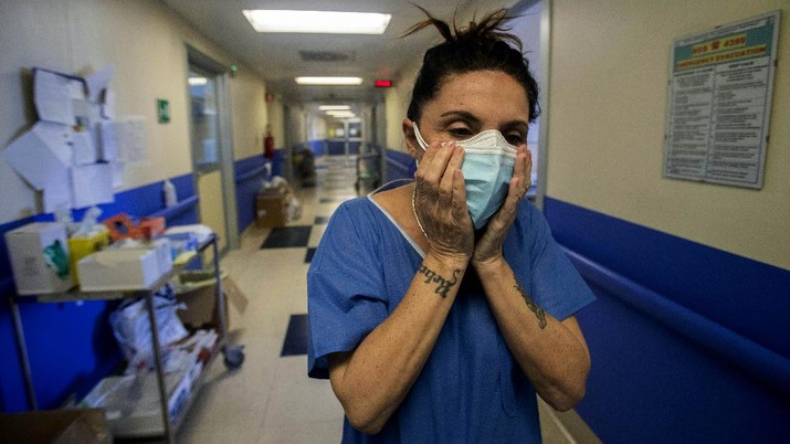 Nurse Cristina Settembrese fixes two masks to her face during her work shift in the COVID-19 ward at the San Paolo hospital in Milan, Italy, April 10, 2020. Settembrese spends her days caring for COVID-19 patients in a hospital ward, and when she goes home, her personal isolation begins by her own choice. (AP Photo/Luca Bruno)