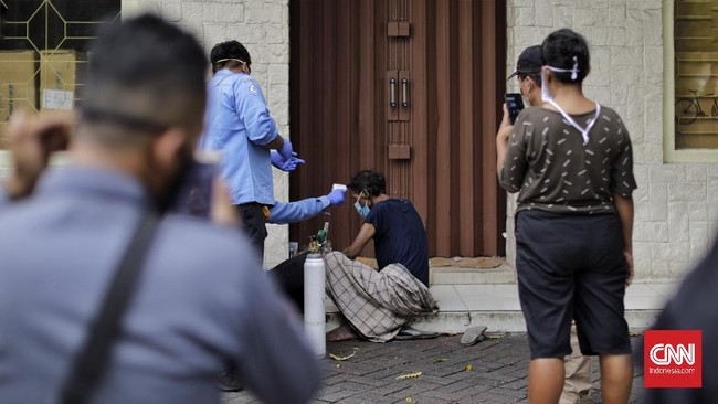 Saat petugas medis melakukan deteksi kesehatan dini sebelum mengevakuasi tunawisma, terlihat warga--setidaknya 10 orang--yang ikut memantau dari jarak sekitar 5-6 meter. Adapula yang mengabadikan peristiwa itu menggunakan kamera ponsel. (CNNIndonesia.com/Adhi Wicaksono)