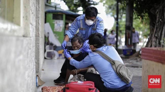 Petugas medis melakukan evakuasi itu setelah mendapatkan laporan dari warga ada tunawisma yang terlihat sesak napas dan demam di kawasan Pasar Baru. Jakarta Pusat. (CNNIndonesia.com/Adhi Wicaksono)