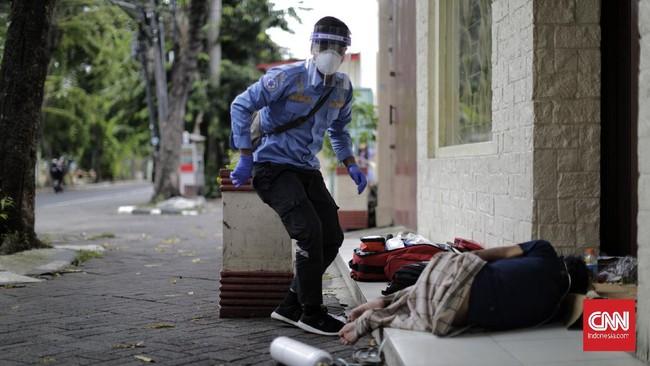 Petugas medis dari Ambulans Gawat Darurat Dinkes DKI Jakartamengevakuasi seorang tunawisma di kawasan Pasar Baru. Jakarta, Selasa, 21 April 2020. Pada 2019 lalu, Kemensos memperkirakan ada 77.500 tunawisma di kota-kota besar Indonesia, termasuk DKI Jakarta. (CNNIndonesia.com/Adhi Wicaksono)
