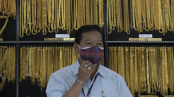 A Thai shopkeeper talks to customer who sold gold necklace to the gold shop in Bangkok, Thailand, Thursday, April 16, 2020. With gold prices rising to a seven-year high, many Thais have been flocking to gold shops to trade in their necklaces, bracelets, rings and gold bars for cash, eager to earn profits during an economic downturn.(AP Photo/Sakchai Lalit)