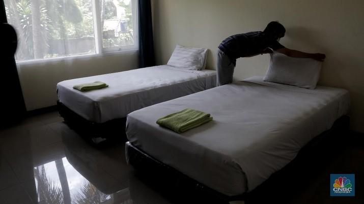 Petugas merapikan ruangan yang akan dijadikan tempat tinggal sementara bagi tenaga medis penanganan Covid-19 di SMKN 57 Jakarta, Rabu (22/4) (CNBC Indonesia/Muhammad Sabki)