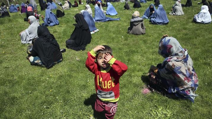 Warga Afghanistan menunggu untuk menerima gandum gratis yang disumbangkan oleh pemerintah Afghanistan menjelang bulan puasa Ramadhan. (AP/Rahmat Gul)