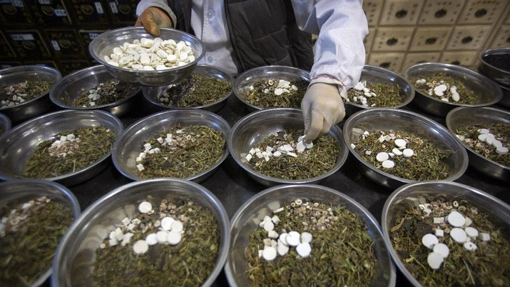 In this March 13, 2020 photo, bowls containing prescriptions for traditional Chinese medicine preparations are stacked on a counter at the Bo Ai Tang traditional Chinese medicine clinic in Beijing. With no approved drugs for the new coronavirus, some people are turning to alternative medicines, often with governments promoting them. (AP Photo/Mark Schiefelbein)