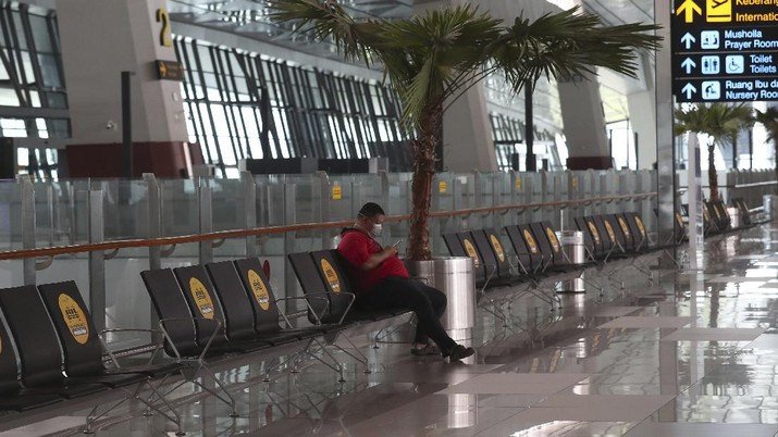 A man sits an empty arrival gate at Soekarno-Hatta International Airport in Tangerang, Indonesia, Indonesia on Friday, April 24, 2020. Indonesia is suspending passenger flights and rail service as it restricts people in the world's most populous Muslim nation from traveling to their hometowns during the Islamic holy month of Ramadan because of the coronavirus outbreak.(AP Photo/Tatan Syuflana)