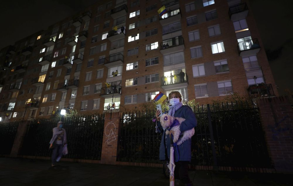 Residents watch a movie from their apartments during a lockdown to help contain the spread of the new coronavirus in Bogota, Colombia, Wednesday, April 22, 2020. The company Cine Colombia set up a giant screen so that people can enjoy a movie projected outside from the comfort and safety of their apartment balconies. (AP Photo/Fernando Vergara)
