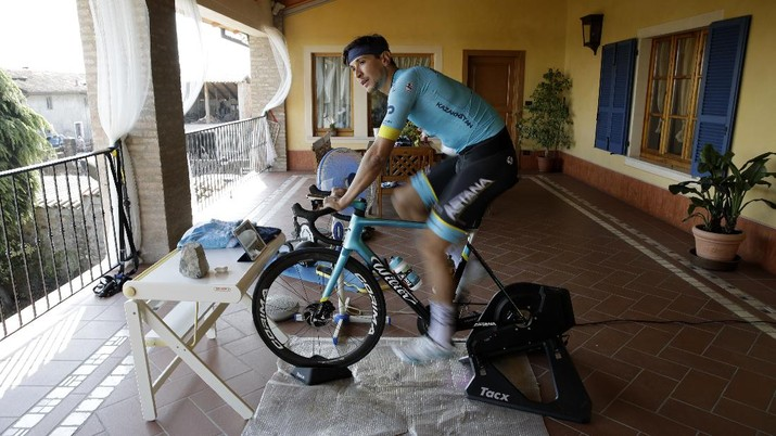 In this image taken on Tuesday, April 14, 2020, Italian professional cyclist Davide Martinelli, collects medicine at a pharmacy to be delivered to residents in Rovato, near Brescia, Northern Italy. There are no fans lining the road. No teammates providing support. And no race to win. Professional cyclist Davide Martinelli has achieved a moral victory, though, by using his bike to help deliver medicine to elderly residents of his hometown in northern Italy during the coronavirus pandemic. (AP Photo/Luca Bruno)