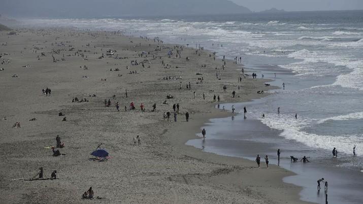 Warga Amerika Serikat berjalan-jalan di Pantai Huntington, California, meski sedang terjadi wabah virus corona. AP/Marcio Jose Sanchez