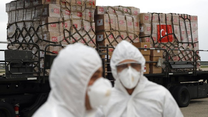 Flight crew members stand on a tarmac in front of a donation of medical supplies from Turkey, Tuesday, April 28, 2020, at Andrews Air Force Base, Md. The donation to help fight the new coronavirus in the United States included surgical masks, sanitizers and protective suits. (AP Photo/Patrick Semansky)