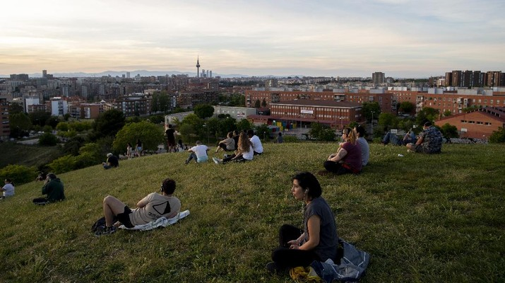People sit in the Cerro del Tio Pio park in Madrid, Spain, Spain, Sunday, May 3, 2020. On Saturday, Spaniards were able to go outdoors to do exercise for the first time in seven weeks since the lockdown began to battle the coronavirus outbreak. (AP Photo/Manu Fernandez)