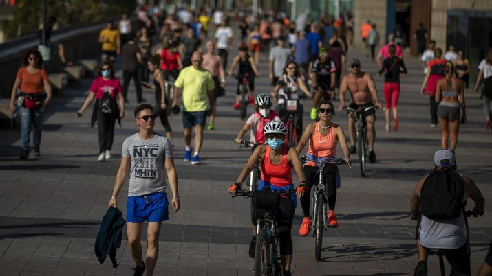 People exercise on a seafront promenade in Barcelona, Spain, Sunday, May 3, 2020. Spaniards have filled the streets of the country to do exercise after seven weeks of confinement to their homes to fight the coronavirus pandemic. People ran, walked, or rode bicycles under a brilliant sunny sky in Barcelona on Saturday, where many flocked to the maritime promenade to get as close as possible to the still off-limits beach. (AP Photo/Emilio Morenatti)