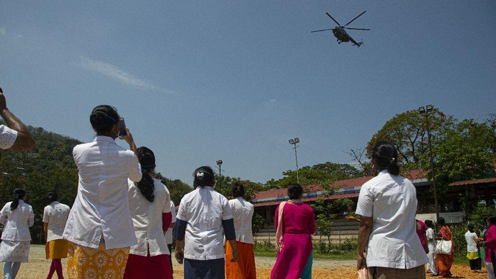 An Indian Air Force helicopter showers flower petals on health workers of Guwahati Medical College Hospital, (GMCH) in Gauhati, India, Sunday, May 3, 2020. The event was part of the Armed Forces' efforts to thank the workers, including doctors, nurses and police personnel, who have been at the forefront of the country's battle against the COVID-19 pandemic. (AP Photo/Anupam Nath)