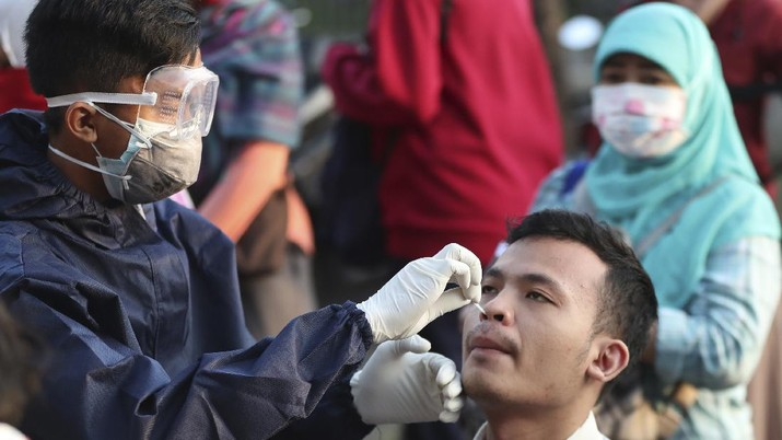 A health worker conducts a swab test for the new coronavirus in Bekasi on the outskirts of Jakarta, Indonesia, Tuesday, May 5, 2020. (AP Photo/Achmad Ibrahim)