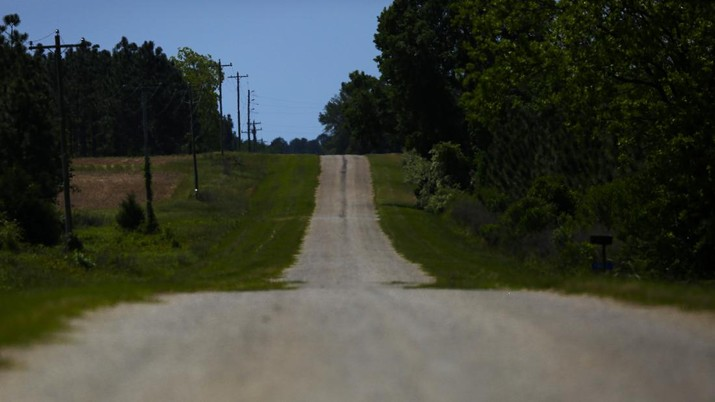 An empty road leading towards a rural countryside of Dawson, Ga., is seen on Friday, April 17, 2020, in Dawson, Ga. Of the 20 counties with the highest death rate in America, six of them are in rural southwest Georgia, where there are no packed skyrise apartment buildings or subways. Other out-of-the way places so far unscathed by the pandemic might believe, like many in Dawson once did, that the virus won't find them out there. But ambulances rushed along country roads, fields and farms in either direction, carrying COVID-19 patients to the nearest hospital, for some an hour away. (AP Photo/Brynn Anderson)