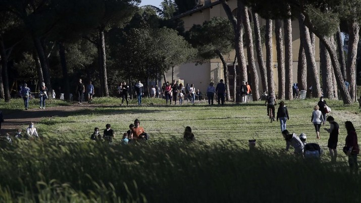 People gather inside Rome's Villa Pamphili park as it reopened after several weeks of closure, part of nationwide limited easing of some lockdown restrictions, on Monday, May 4, 2020. Italy began stirring again Monday after a two-month coronavirus shutdown, with 4.4 million Italians able to return to work and restrictions on movement eased in the first European country to lock down in a bid to stem COVID-19 infections.  (AP Photo/Alessandra Tarantino)