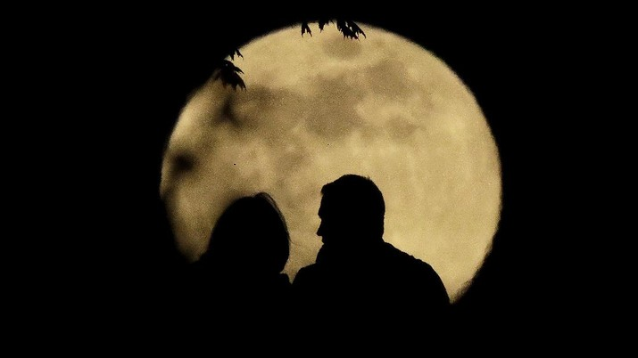 A couple watches the full moon rise Wednesday, May 6, 2020, from a park in Kansas City, Mo. (AP Photo/Charlie Riedel)
