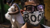 Beberapa aktivis juga memanfaatkan masker sebagai 'wadah' kampanye sosialnya. Berbagai pesan bernuansapolitik mewarnai sejumlah masker. (AP Photo/Ramon Espinosa )