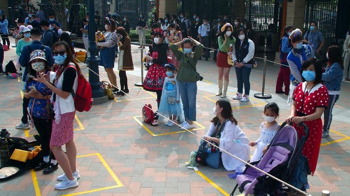 Visitors, wearing face masks, wait to enter the Disneyland theme park in Shanghai as it reopened, Monday, May 11, 2020. Visits will be limited initially and must be booked in advance, and the company said it will increase cleaning and require social distancing in lines for the various attractions. With warmer weather and new coronavirus cases and deaths falling to near-zero, China has been reopening tourist sites such as the Great Wall and the Forbidden City palace complex in Beijing.(AP Photo/Sam McNeil)