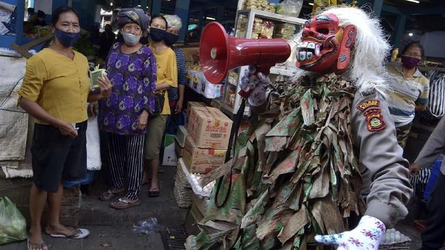 Petugas kepolisian yang mengenakan kostum menyeramkan 'Celuluk' melakukan sosialisasi langkah-langkah pencegahan Covid-19 di Pasar Tradisional Sempidi, Badung, Bali, 12 Mei 2020. Kegiatan tersebut dilakukan untuk mengimbau masyarakat terus melakukan berbagai upaya pencegahan penyebaran COVID-19. (ANTARA FOTO/Fikri Yusuf)