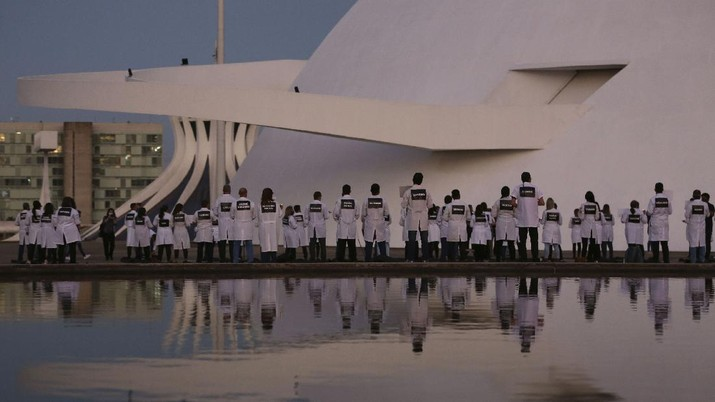 Nurses gather in front of the National Museum holding placards with the names of their colleagues who died in their fight against the new coronavirus pandemic, during a protest marking International Nurses Day, in Brasilia, Brazil, Tuesday, May 12, 2020. (AP Photo/Eraldo Peres)