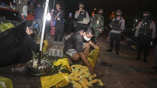 Petugas menasihati para pedagang tentang jam malam saat penerapan hari pertama PSBB di pasar tumpah, Palangkaraya, Kalimantan Tengah, 11 Mei 2020. Kegiatan patroli malam tersebut mengimbau warga untuk mematuhi peraturan PSBB sebagai upaya memutus rantai penyebaran Covid-19. (ANTARA FOTO/Makna Zaezar)