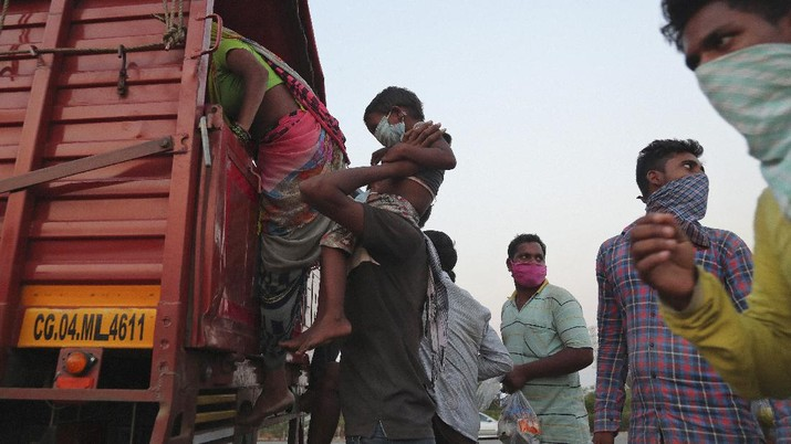 A migrant worker from Chhattisgarh state helps a child climb onto a truck to travel to their villages hundreds of miles away, during a nationwide lockdown to curb the spread of new coronavirus on the outskirts of Hyderabad, India, Tuesday, May 12, 2020. The lockdown that began March 25 sent an exodus of workers from its huge informal sector fleeing the cities to their ancestral homes in the countryside. Economists say unemployment reached 24.7% this week. (AP Photo/Mahesh Kumar A)