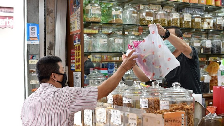 A man wearing a face mask looks at traditional Chinese medicinal products inside a Chinese medical hall in Singapore's Chinatown district on Tuesday, May 12, 2020. Singapore has allowed selected businesses such as traditional Chinese medicine medical halls, home-based establishments, food manufacturing, selected food retail outlets, laundry services, traditional barbers and pet supplies to reopen May 12 in a cautious rollback of a two-month partial lockdown to curb the spread of COVID-19 infections in the city-state. (AP Photo / YK Chan)