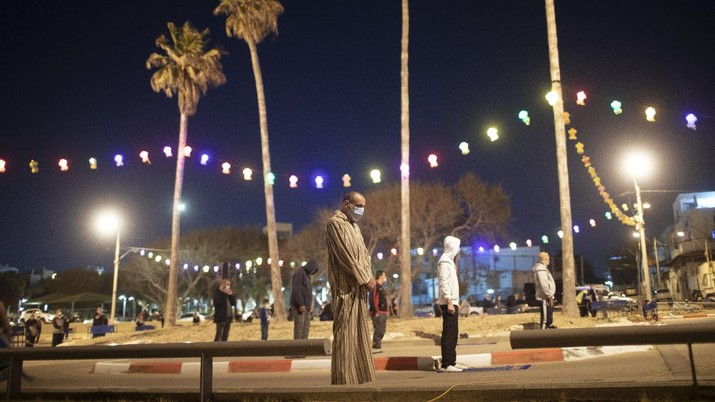 Muslim men keep social distancing as they pray after breaking their daytime fast, at a parking lot as mosques remain closed to prevent the spread of coronavirus pandemic during the holy month of Ramadan, in the mixed Arab Jewish city of Jaffa, near Tel Aviv, Israel, Sunday, May 10, 2020. (AP Photo/Oded Balilty)