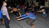 Anggota Polres Gowa memberikan hukuman olah raga fisik kepada warga yang melanggar pemberlakuan jam malam di Kabupaten Gowa, Sulawesi Selatan, Kamis (7/5) dini hari. (ANTARA FOTO/Abriawan Abhe)