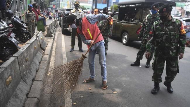 Sanksi kerja sosial bisa dengan menyuruh pelanggar membersihkan fasilitas umum, seperti terjadi di Jakarta, Rabu (13/5). (ANTARA FOTO/Akbar Nugroho Gumay)